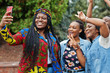 canvas print picture - Group of five african college students spending time together on campus at university yard. Black afro friends making selfie on phone. Education theme.