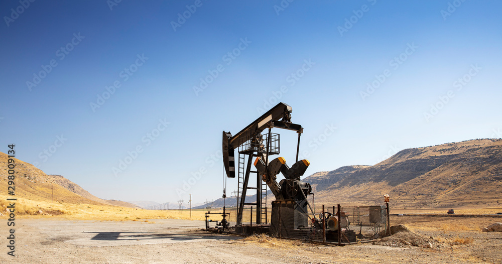 Fototapety, obrazy: Oil drilling derricks at desert oilfield. Crude oil production from the ground. Oilfield services contractor. Oil drill rig and pump jack. Petroleum production, natural gas, liquids, NGL, additive.
