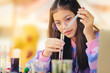 Asian teenage girl in elementary science class doing chemical experiment test try to drop color water to test tubes. Education concept