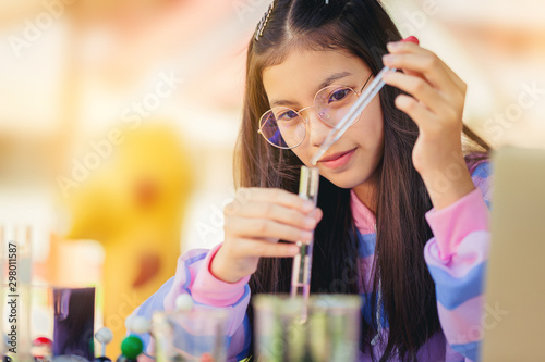 Leinwand Poster  Asian teenage girl in elementary science class doing chemical experiment test try to drop color water to test tubes