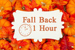 Leinwandbild Motiv Fall Back 1 hour time change message on a metal sign on pumpkins