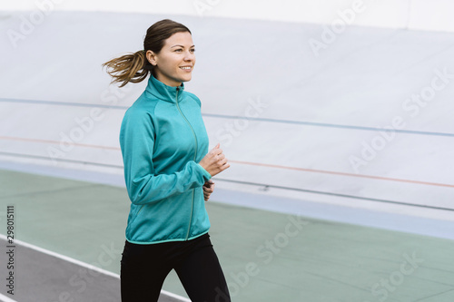 Young adult sportswoman training outdoor in city