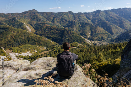 Relaxed tourist admiring the view from the mountain top,hiking concept, Panoramic view landscape from mountain, Bulgaria
