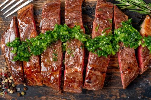 Fotografie, Obraz  Roast sliced beef Steak medium rare Striploin with chimichurri sauce close up