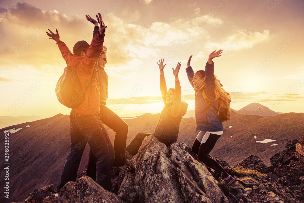 Fototapety, obrazy: Four happy hikers on mountain top at sunset