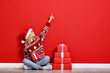 canvas print picture - happy young cheerful girl laughs and jumps in christmas hat and with  gift on  red   background.