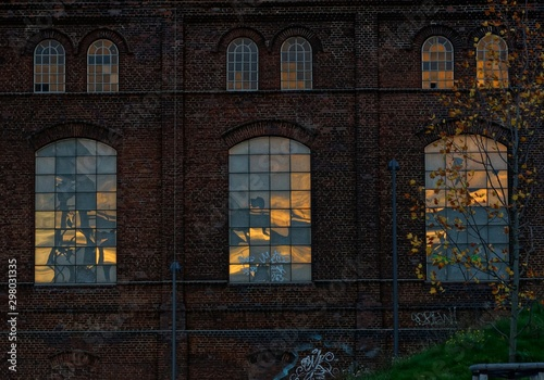 Beautiful shot of a brick building with big windows and graffiti on the walls