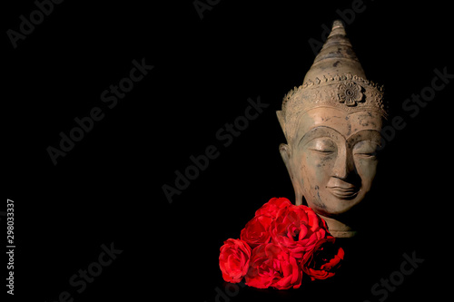 Peace and love. Traditional Buddha head statue with red roses.
