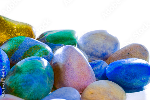 Synthetic nature. Polished colored beach pebbles selective focus close-up.