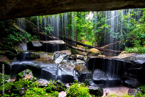 A small waterfall in the deep forest of the border of Thailand and Cambodia,ASIA.Khun Sri waterfall in tropical forest,Sisaket province,Thailand. Leaf moving low speed shutter blur.