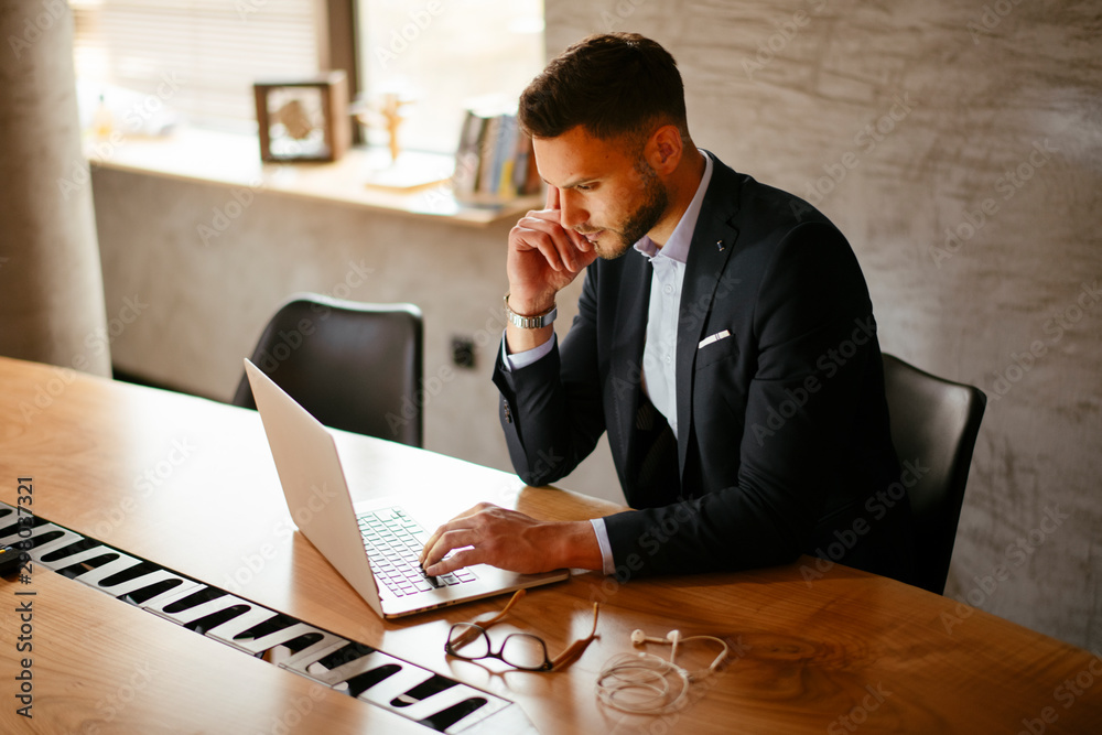 Fototapeta Young businessman using laptop in his office