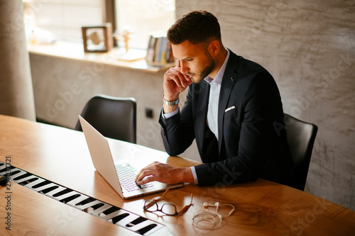 Young businessman using laptop in his office