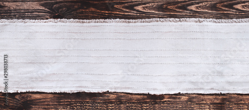 Grey fabric runner on an old wooden rustic table background with copy space. Top view.