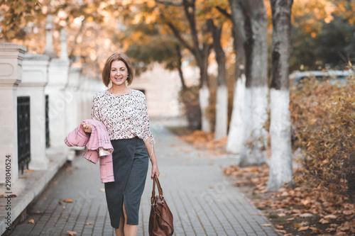 Smiling woman 50-55 year old walking in street wearing suit holding bag outdoors Fototapet