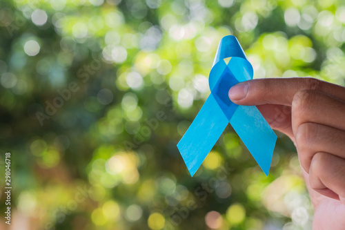 Blue ribbon in the hands of men. Prostate cancer awareness. Tablou Canvas