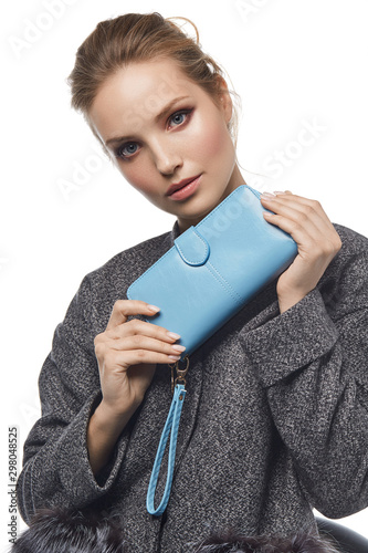 Valokuva Medium close-up shot of a young brown-haired European lady in a gray mottled jacket with a textured blue leather wallet with a buckle opening closure and a wristlet strap handle in her hands