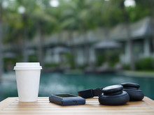 Takeaway Cup Of Coffee With Music Player And Headphones On Table At Resorts Background