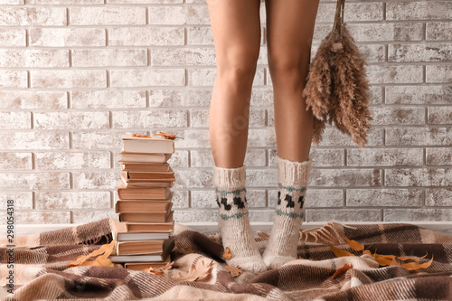 Obraz na plátně  Young woman with stack of books standing on plaid near brick wall
