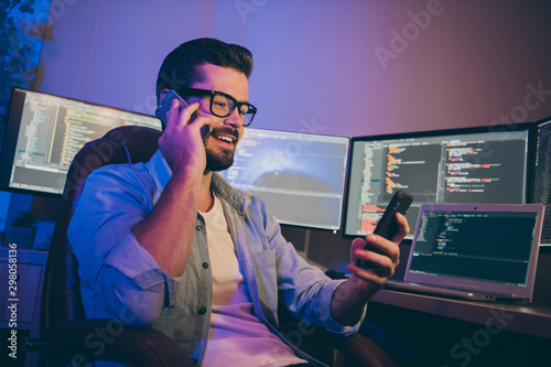 Fototapety, obrazy: Photo of it specialist guy working late at night sitting chair many monitors speaking telephone teammate reading new task in slack corporate chat night office indoors