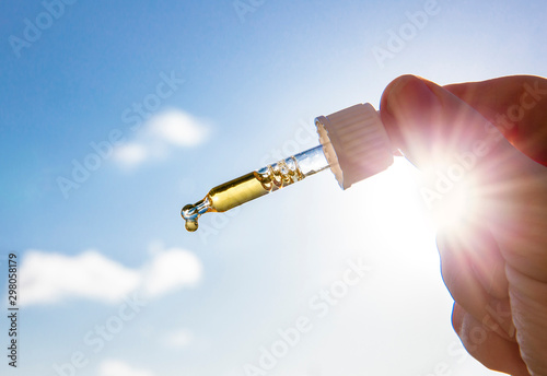 Fototapeta Hand holding dropper pipette with nice golden liquid D-vitamin against sun and blue sky on sunny day. Vitamin D keeps you healthy while lack of sun in winter, cure concept. obraz