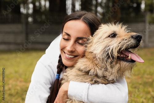 Female volunteer with homeless dog at animal shelter outdoors Wallpaper Mural