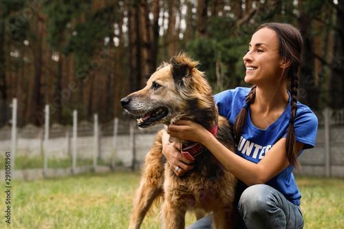 Obraz na płótnie Female volunteer with homeless dog at animal shelter outdoors