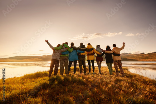 Happy big family hugging together in mountains