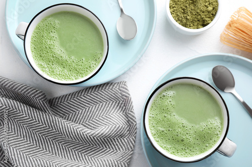 Leinwand Poster Flat lay composition with tasty matcha green tea latte on white table