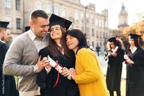 Fotografia  Happy student with parents after graduation ceremony outdoors