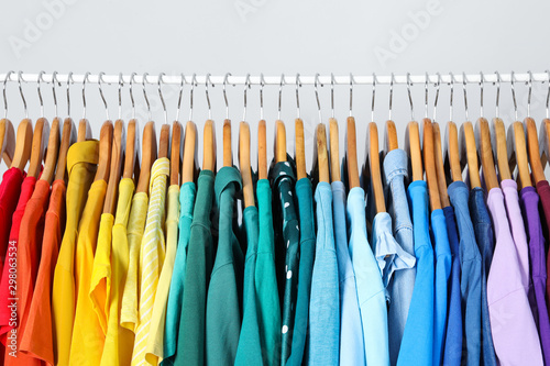 Rack with bright clothes on light blue background. Rainbow colors Tapéta, Fotótapéta