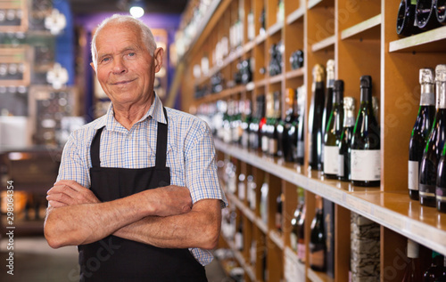 Cuadros en Lienzo Portrait of confident senior vintner posing smiling in wineshop interior