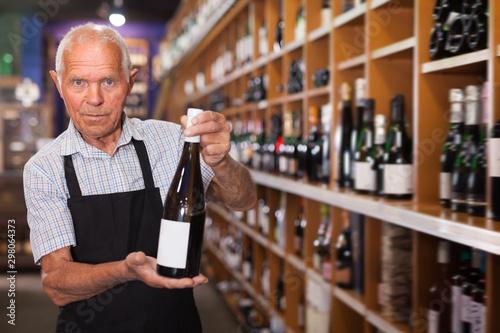 Fotografía  Confident elderly male owner of wine shop