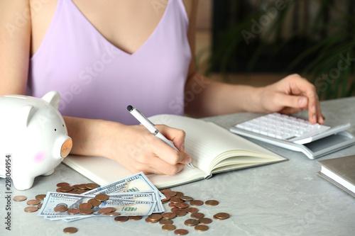 Fotografía  Woman counting coins at grey marble table, closeup. Money savings