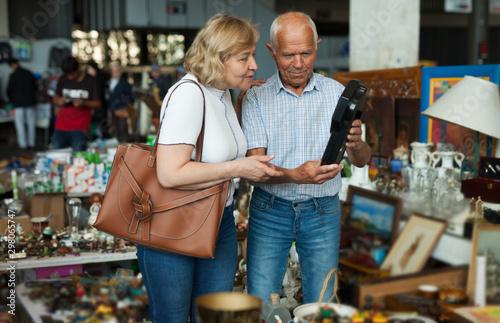 Foto Elderly couple in flea market chooses antique items
