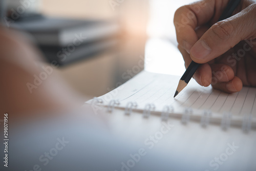 Fotomural  Businessman writing on notebook