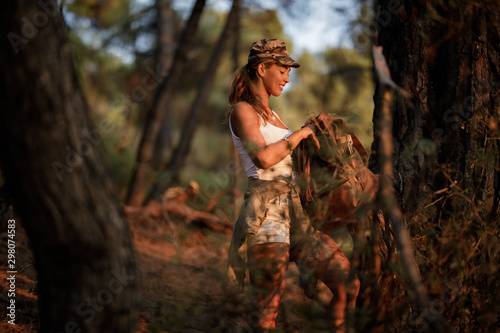 Young woman hiking and taking something from her backpack. Slika na platnu