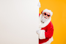 Portrait Of Funny Funky Christmas Father In Red Hat Headwear Look Behind White Wall Poster Advertise Winter X-mas Shopping Seasonal Miracle Sales Discounts Isolated Over Bright Color Background