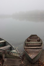 Fishing Old Boats On The River Bank In The Fog