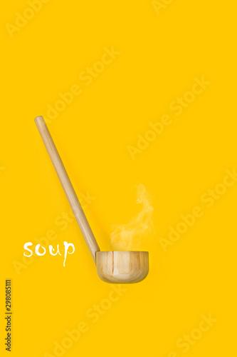 Fototapeta  Cuchara de madera con humo y texto soup sobre fondo amarillo vista desde de fren