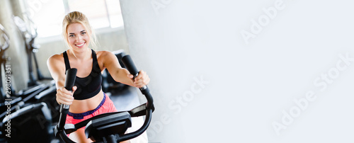 Fototapeta premium Kobiety noszące odzież sportową ćwiczące, kręcące się na rowerze elektrycznym na siłowni Dla dobrego zdrowia Mają piękny kształt I pozwalają rozluźnić mięśnie. skopiuj miejsce na tle transparentu.