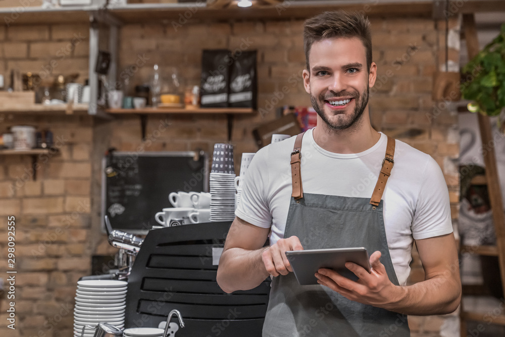 Fototapeta Smiling young entrepreneur wearing an apron near counter of his cafe and using digital tablet