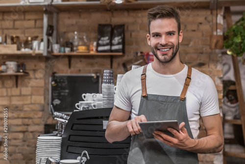 Fotomural  Smiling young entrepreneur wearing an apron near counter of his cafe and using d