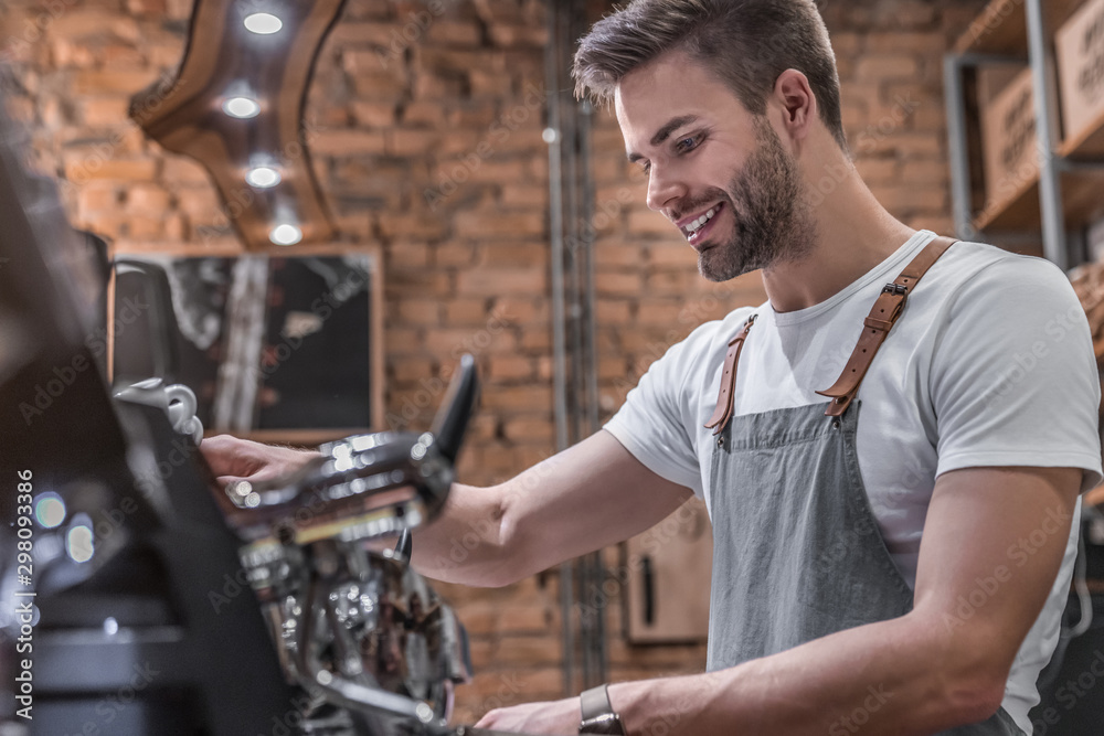 Fototapeta Side view shot of a male barista making a cup of coffee