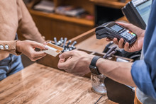 Male Barista Holding Credit Card Reader Machine With Female Customer Credit Card For Payment.