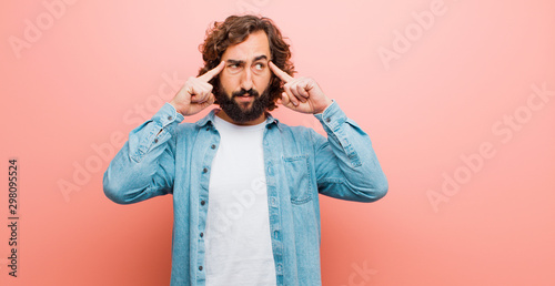 Obraz young bearded crazy man feeling confused or doubting, concentrating on an idea, thinking hard, looking to copy space on side against flat color wall - fototapety do salonu