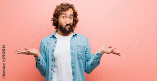young bearded crazy man feeling puzzled and confused, doubting, weighting or cho Fototapeta