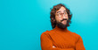 young bearded crazy man feeling happy, proud and hopeful, wondering or thinking, looking up to copy space with crossed arms against flat color wall