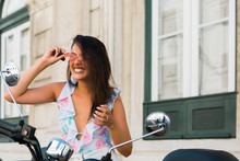Carefree Beautiful Funny Woman In Sunglasses Looking At Motorbike Mirror On Street