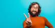 young bearded crazy man smiling and looking happy, carefree and positive, gesturing victory or peace with one hand against flat color wall