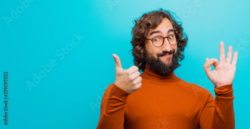 Valokuva  young bearded crazy man feeling happy, amazed, satisfied and surprised, showing